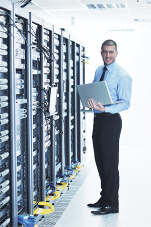 Smiling man holding a laptop and standing next to servers.