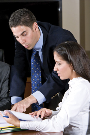 Man looking over a woman's shoulder pointing at paperwork