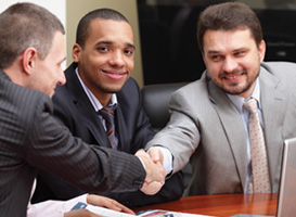 Men shaking hands at a meeting.