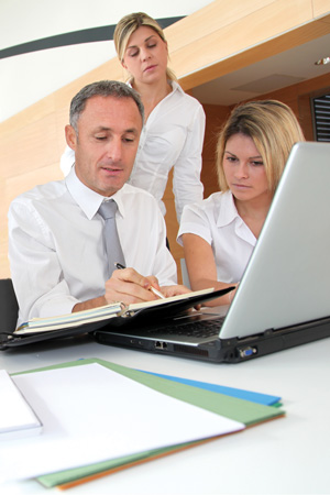 Three people looking over data on a three-ring binder.