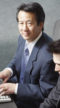 Asian business man typing on a computer.